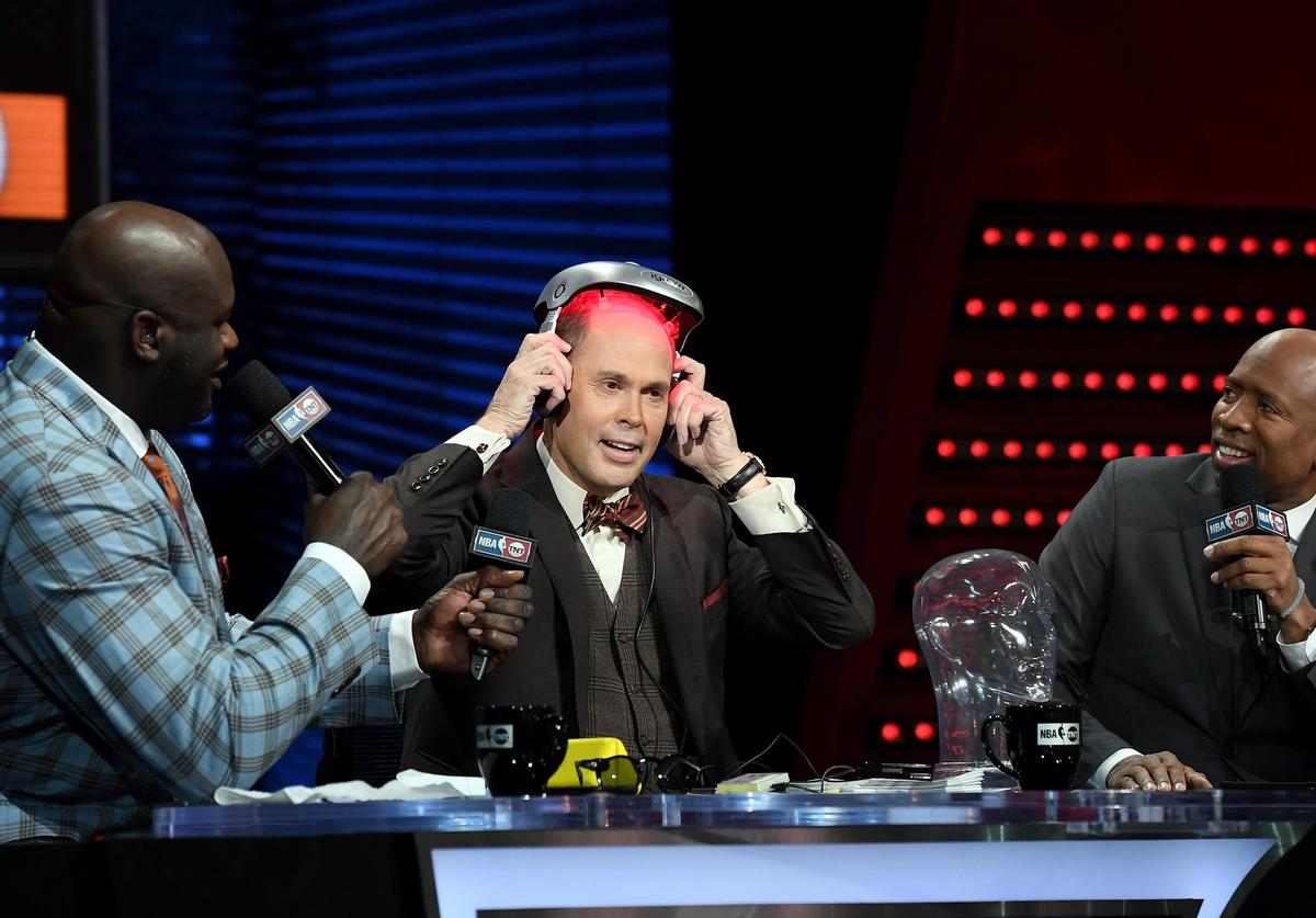 TNT's Inside the NBA host Ernie Johnson (C) puts on an iGrow laser-based hair-growth helmet as NBA analysts Shaquille O'Neal (L) and Kenny Smith (R) look on during a live telecast of 'NBA on TNT' at CES 2017 at the Sands Expo and Convention Center on January 5, 2017 in Las Vegas, Nevada. CES, the world's largest annual consumer technology trade show, runs through January 8 and features 3,800 exhibitors showing off their latest products and services to more than 165,000 attendees.