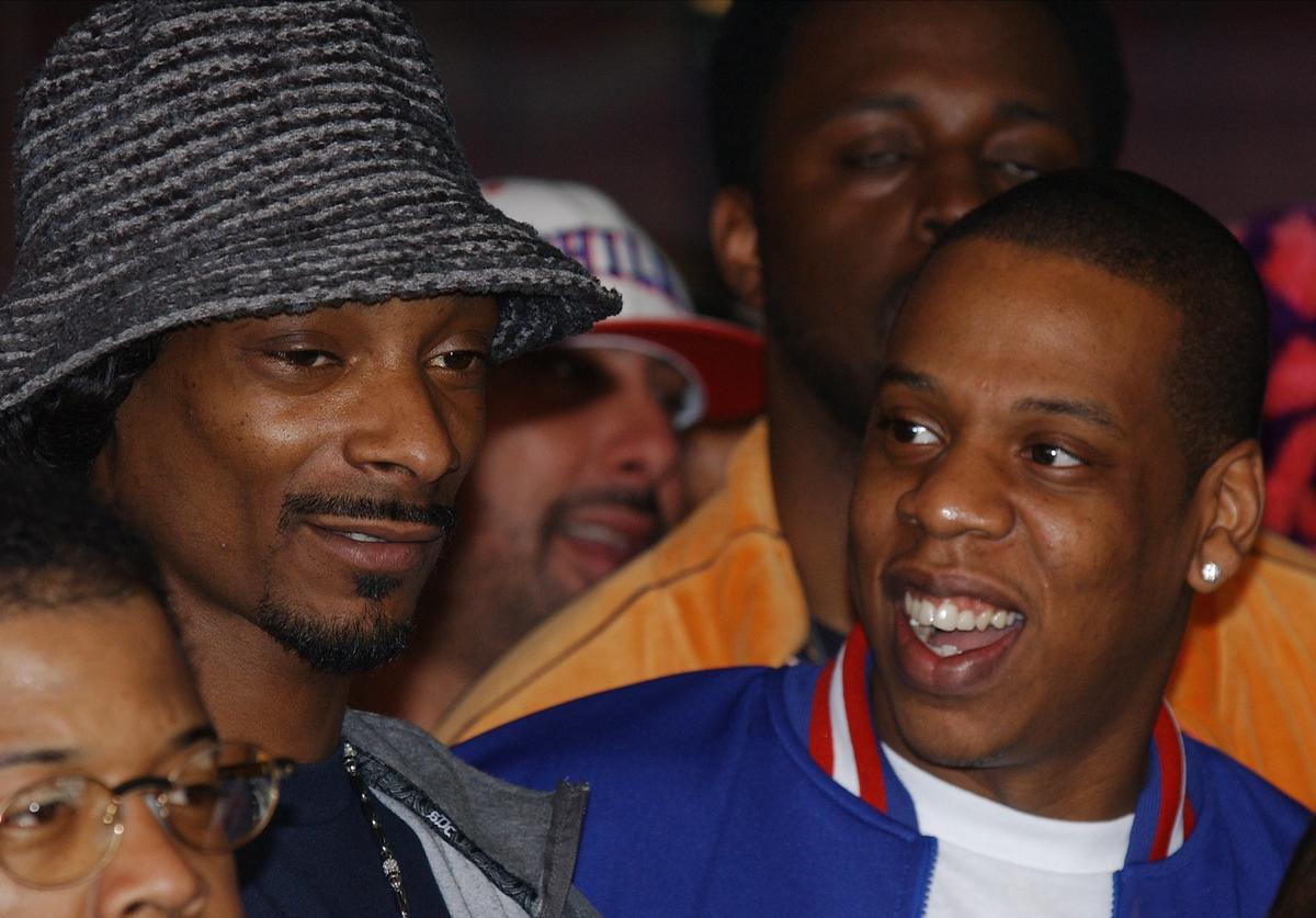 Snoop Doggy Dogg (L) and Jay-Z (R) attend a handprint ceremony for the hip-hop group RUN-DMCs induction into the Hollywood RockWalk February 25, 2002 at the Guitar Center in Hollywood, CA