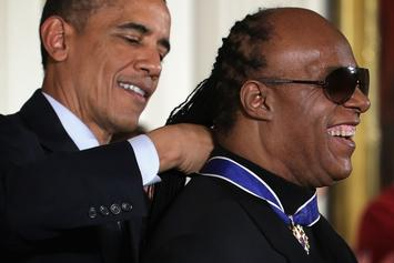 Stevie Wonder Takes A Knee During Performance Of National Anthem