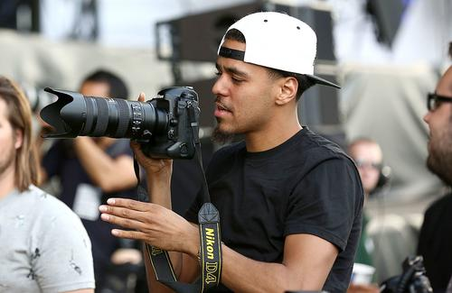 Rapper J Cole borrows a photographer's camera in the photo pit during the Outkast performance stage at Wireless Festival at Finsbury Park on July 6, 2014 in London, United Kingdom.