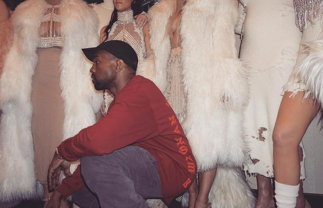 Kanye West crouching in front of Kardashians