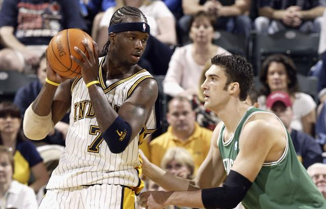 Jermaine O'Neal #7 of the Indiana Pacers backs in against the Chris Mihm #4 of the Boston Celtics on April 17, 2004 at the Conseco Fieldhouse in Indianapolis, Indiana. The Pacers beat the Celtics 104-88.